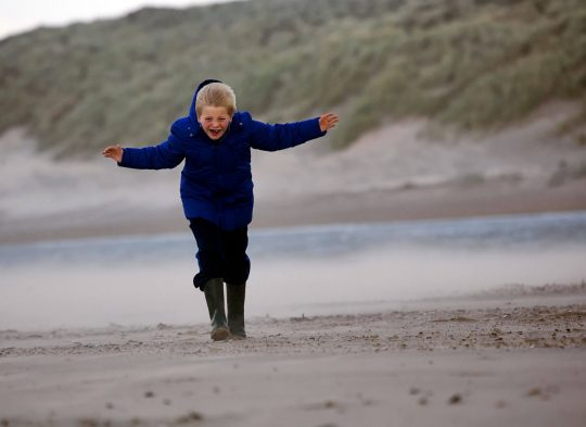 Kind op strand in stevige wind